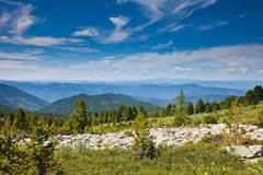 Ajardine o pico do formulário da montanha sob o céu azul Imagens de Stock