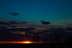 Ajardine o por do sol sobre a estrada e o campo O carro na estrada Fundo Foto de Stock Royalty Free