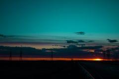 Ajardine o por do sol sobre a estrada e o campo O carro na estrada Fundo Imagem de Stock Royalty Free
