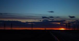 Ajardine o por do sol sobre a estrada e o campo O carro na estrada Fundo Fotos de Stock Royalty Free