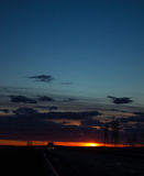 Ajardine o por do sol sobre a estrada e o campo O carro na estrada Fundo Fotografia de Stock Royalty Free