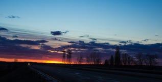 Ajardine o por do sol sobre a estrada e o campo O carro na estrada Fundo Foto de Stock