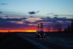 Ajardine o por do sol sobre a estrada e o campo O carro na estrada Fundo Fotos de Stock