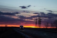 Ajardine o por do sol sobre a estrada e o campo O carro na estrada Fundo Fotografia de Stock