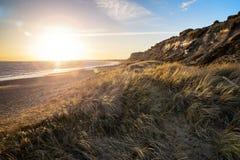 Ajardine o por do sol vívido sobre a praia e os penhascos com o fla adicionado da lente Imagens de Stock