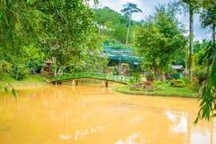 Ajardine o projeto de relaxam o jardim tropical com banco e ponte de rio Fotografia de Stock Royalty Free