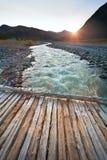 Ajardine o rio da montanha e uma ponte de madeira no por do sol Imagem de Stock