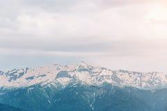 Ajardine, o tempo nebuloso, picos de montanha alta com neve Imagem de Stock Royalty Free