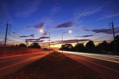 Ajardine o tráfego na estrada no tempo do crepúsculo da noite Imagens de Stock Royalty Free