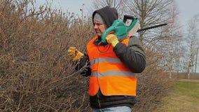 Ajardine o trabalhador com o cortador do arbusto perto do arbusto no parque vídeos de arquivo
