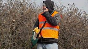 Ajardine o trabalhador com o cortador do arbusto que fala no telefone celular vídeos de arquivo