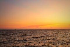 Ajardine, opinião do mar na luz alaranjada bonita do por do sol A Há navios de carga que passam completamente Imagem de Stock Royalty Free