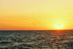 Ajardine, opinião do mar na luz alaranjada bonita do por do sol A Há navios de carga que passam completamente Fotografia de Stock Royalty Free