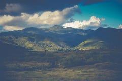 Ajardine a opinião do panorama em montanhas com as nuvens no effe do vintage Fotos de Stock