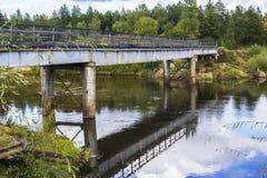 Ajardine a ponte oxidada velha do ferro do fundo sobre uma floresta do rio Foto de Stock