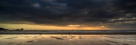 Ajardine a praia da baía de Rhosilli do panorama no por do sol com céu temperamental Fotografia de Stock