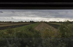 Ajardine a través de una ventana de la mitad-windowed del tren Foto de archivo