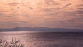 Ajardine a vista colorida do céu azul com nuvens e de um mar com r Foto de Stock Royalty Free