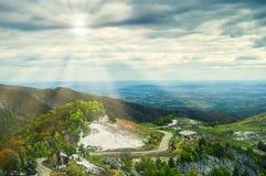 Ajardine a vista com por do sol, nascer do sol, o céu, as nuvens, os picos de montanha, e a floresta Fotos de Stock Royalty Free
