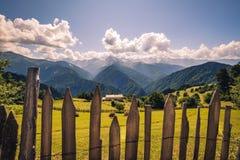 Ajardine a vista das montanhas, dos prados e da casa de campo em Svaneti, Geórgia Fotografia de Stock