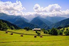 Ajardine a vista das montanhas, dos prados e da casa de campo no parque nacional de Svaneti, Geórgia Imagem de Stock