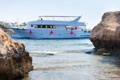 Ajardine a vista das rochas na praia, iate no mar no backgr Imagens de Stock Royalty Free