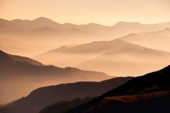Ajardine a vista de montes da montanha enevoada no por do sol Imagem de Stock Royalty Free