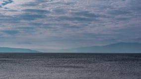 Ajardine a vista do céu azul com nuvens e de um mar com ressaca áspera Foto de Stock Royalty Free
