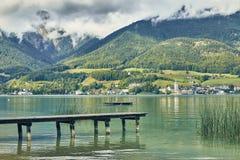 Ajardine a vista do lago colorido ciano Wolfgangsee com uma plataforma da costa da vila de Gschwendt em Áustria fotografia de stock royalty free