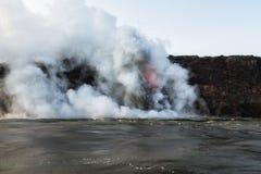 Ajardine a vista do oceano entrando da lava com explosões Imagem de Stock
