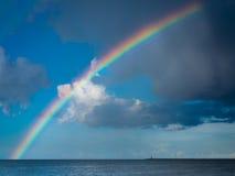 Ajardine a vista no céu com o arco-íris no mar Foto de Stock