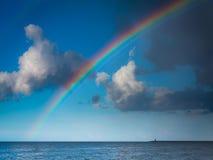 Ajardine a vista no céu com o arco-íris no mar Imagens de Stock Royalty Free