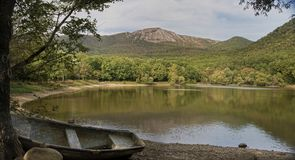 Ajardine a vista no lago, nas montanhas e no barco velho Imagens de Stock