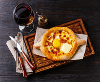Ajarian Khachapuri cheese pastry and wine. Ajarian Khachapuri traditional Georgian cheese pastry and wine on burned black wooden background Stock Image