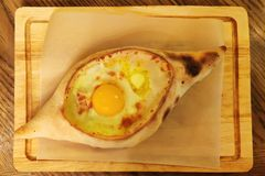 Ajarian Khachapuri Georgian cheese pastry with eggs and oil on cutting board. Homemade bakery. Single object royalty free stock photos