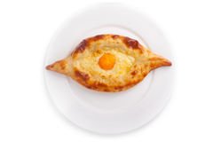 Ajarian khachapuri Georgian cheese pastry. Top view of Ajarian khachapuri, Georgian cheese pastry, filled with cheese and topped with a soft-boiled egg and royalty free stock photo