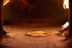 Ajarian-khachapuri mit Käse kochte in brennendem Brennholz des Ofens Stockbilder