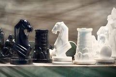 Ajedrez blanco y negro puesto en fondo ligero Imagenes de archivo