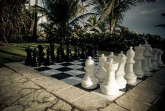 Ajedrez de tamaño natural en el paraíso, blanco contra negro Imagen de archivo