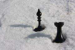 ajedrez en la nieve figuras negras en blanco Fotografía de archivo libre de regalías