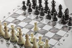 Ajedrez Los blancos están comenzando Tablero blanco con las figuras del ajedrez en él Foto de archivo
