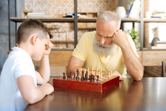 Ajedrez que juega de abuelo concentrado con su nieto Fotos de archivo