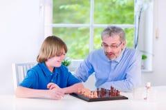 Ajedrez que juega de abuelo feliz con su nieto Imagen de archivo libre de regalías