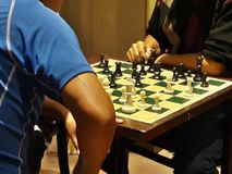 Ajedrez que juega la competencia en el tablero de ajedrez del café imagen de archivo