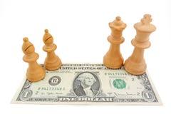 Ajedrez y dólar: Obispos ligeros en obispos, rey y reina de un billLight del dólar de EE. UU. en una cuenta de dólar de EE. UU. Fotografía de archivo libre de regalías