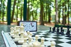 Ajedrez y reloj del ajedrez en la tabla en el parque foto de archivo libre de regalías