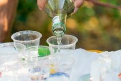 Ajerówka nalewa w plastikowych szkła Butelka w mężczyzna ` s ręce zdjęcie royalty free