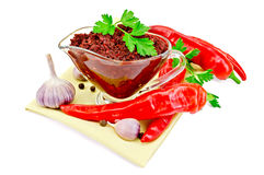 Ajika in a glass gravy boat on a napkin Royalty Free Stock Images