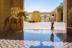 Ajman Agosto 2016 L'impiegato ed il cavallo dorato della scultura davanti all'hotel Ajman Saray Fotografia Stock