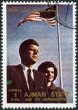 AJMAN - 1972: shower John F Kennedy (1917-1963) och fru Jacqueline Lee Jackie Bouvier (1929-1994) Arkivbilder